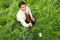 A mixed ethnicity businessman holding the plug end of an extension cord next to an electrical outlet in the ground in a grassy field.