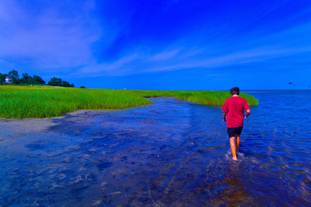 15 year old boy walking in the water at Rock Harbor, Orleans, Cape Cod, Massachusetts, USA