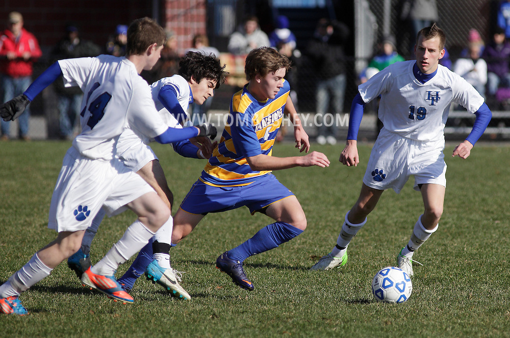Lansing's Cobi Byrne, center, dribbles the ball through three Hoosick Falls players during a Class C state semifinal boys' soccer game at Faller Field in Middletown on Saturday, Nov. 17, 2012.