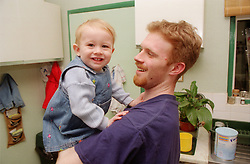 Teenage father holding young daughter in kitchen smiling,