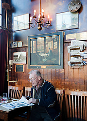 Man reading newspaper inside very old 17th Century Cafe Paneneiland on Prisengracht canal in Amsterdam Netherlands