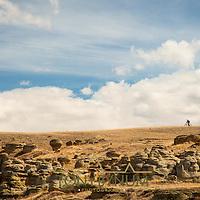 man riding bike on a ridge though badlands of montana big sky, central montana,