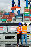 Athens, Greece. Container Terminal. Agents discussing logistics matters quayside.