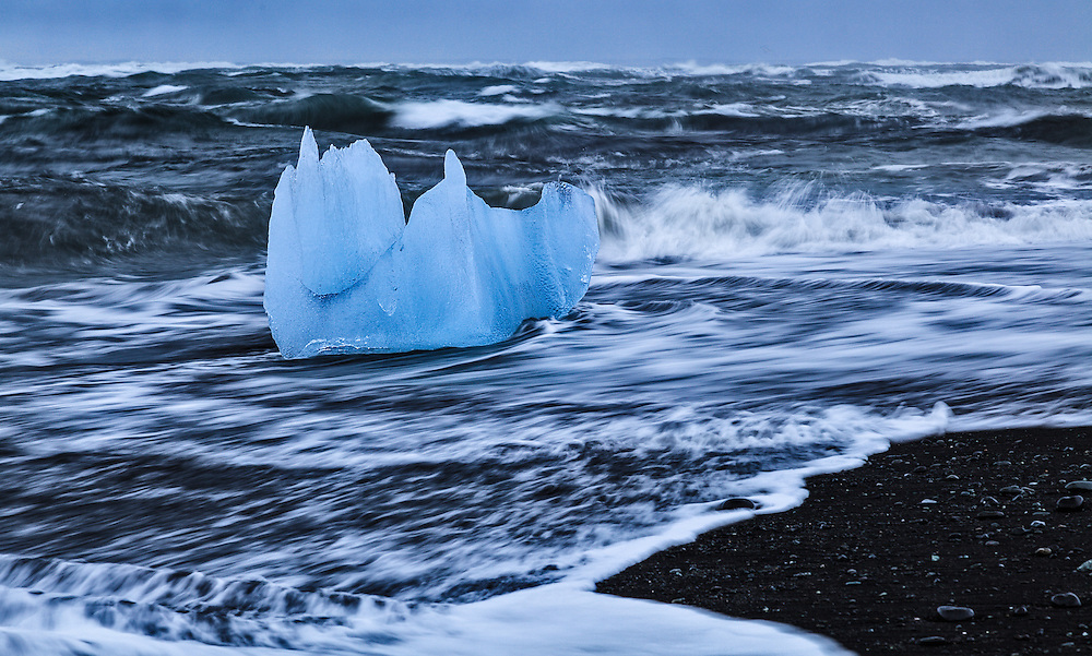 A piece of the Jokulsarlon glacier being swept out to sea from the black sand of Jokulsarlon Beach.