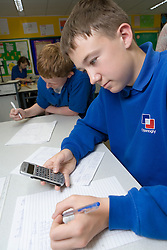 Student in physic class using calculator and recording results of experiment,