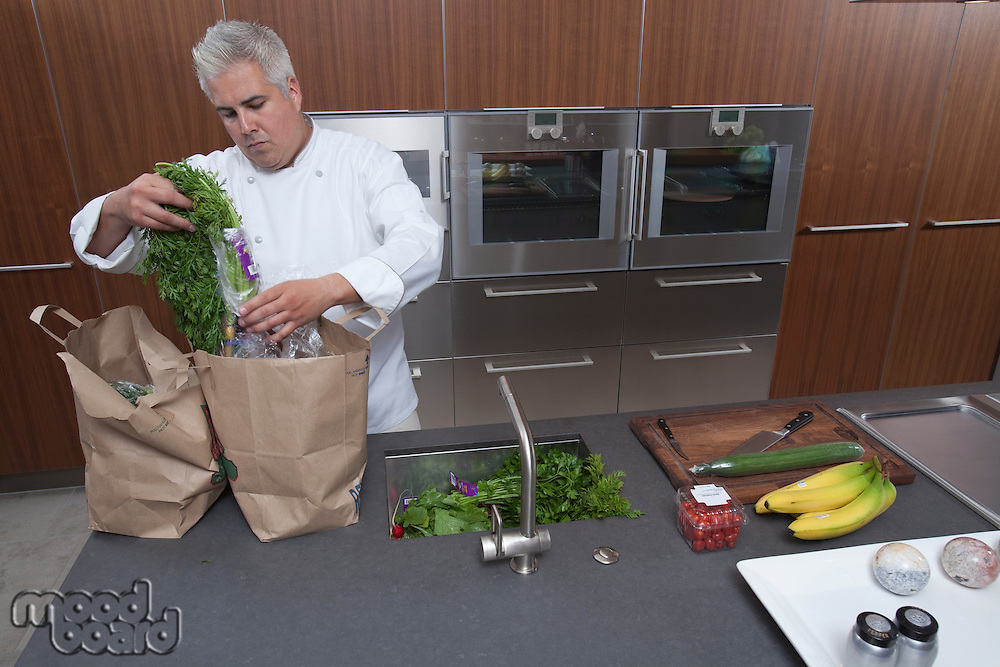 Mid- adult chef unpacking groceries