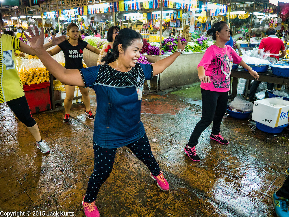 "21 DECEMBER 2015 - BANGKOK, THAILAND: A woman participates in an aerobics class in Pak Khlong Talat, also called the Flower Market. The market has been a Bangkok landmark for more than 50 years and is the largest wholesale flower market in Bangkok. Aerobics classes and fitness programs are common in Thai markets and parks. A recent renovation resulted in many stalls being closed to make room for chain restaurants to attract tourists. Now Bangkok city officials are threatening to evict sidewalk vendors who line the outside of the market. Evicting the sidewalk vendors is a part of a citywide effort to ""clean up"" Bangkok.       PHOTO BY JACK KURTZ"