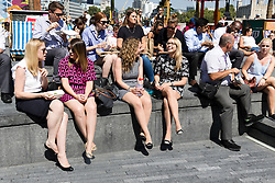 © Licensed to London News Pictures. 17/08/2016. LONDON, UK.  Crowds of tourists and office workers enjoy the hot and sunny summer weather on the south bank near Tower Bridge in London this lunchtime.  Photo credit: Vickie Flores/LNP
