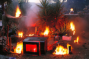 (1997). Broken and obsolete machines formerly stored in Peter Menzel's and Faith D'Aluisio's garage set ablaze for a Christmas card in 1997. Napa Valley, California.