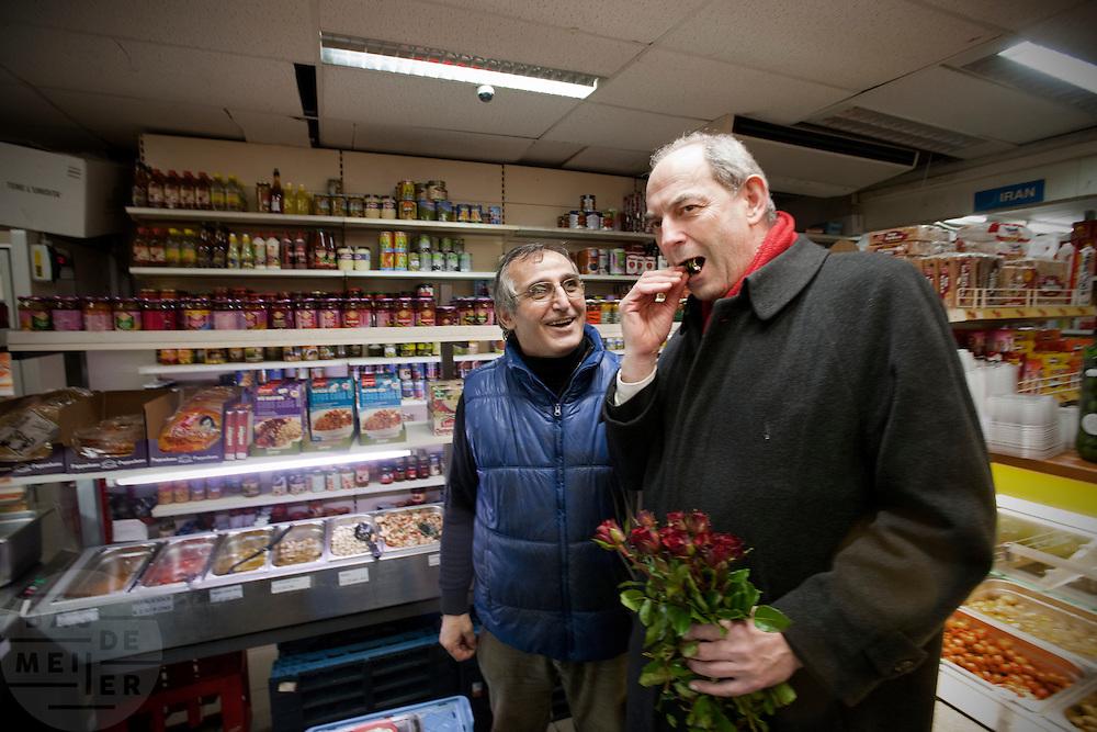 Job Cohen krijgt van een allochtone winkelier aan de Kanaalstraat in Utrecht een lekkernij aangeboden. Cohen voert samen met Marleen Barth en Bert de Vries voor de PvdA campagne in Utrecht voor de Provinciale Statenverkiezingen.<br /> <br /> Job Cohen, leader of the Dutch Labour party PvdA, is tasting a delicacy in a shop. Cohen is campaigning for the next elections.