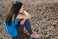 Young woman sitting on beach side view elevated view
