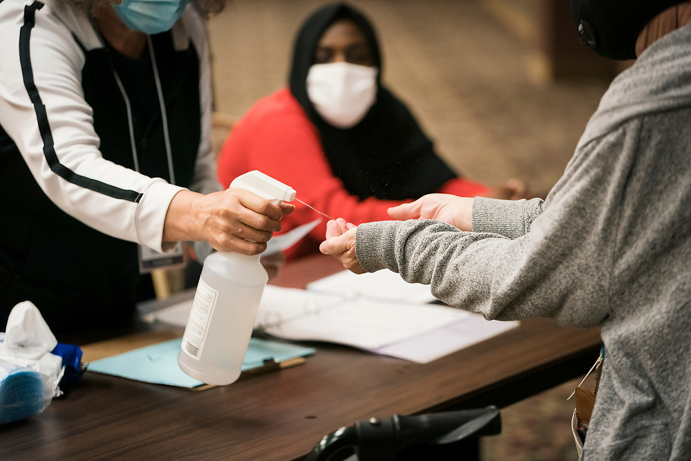 An election worker sanitizes the hands of a voter at a polling location in Minneapolis, Minnesota, U.S., on Tuesday, Aug. 11, 2020. Photographer: Ben Brewer/Bloomberg
