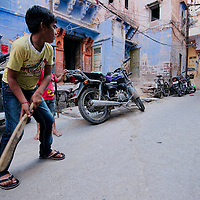 Boys playing cricket on the street