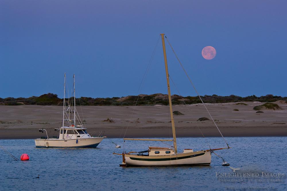 Full moon setting at dawn over sailboats in Morro Bay, California
