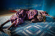 A Ghanaian woman lies on the floor of her bedroom - a dark, empty room devoid of any belongings and only a sheet on the ground for a bed. <br />