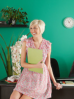 Portrait of young office worker on desk with folder