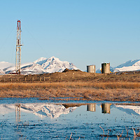 drill rigs set up to frack oil on the blackfeet reservation with rising wolf mountain glacier national park, montana, usa  the background conservation photography - blackfeet oil
