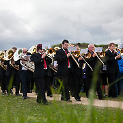 A REQUIEM FOR THE FOGHORN, PERFORMED BY SEVENTY FIVE BRASS PLAYERS, A FOGHORN AND AN ARMADA OF SHIPS<br /> A project by Danish artist, Lise Autogena, in collaboration with Joshua Portway and composer Orlando Gough. <br /> Ships horns from an armada of vessels off-shore, seventy five brass players on-shore and the Souter Lighthouse Foghorn  performed a Foghorn Requiem, an ambitious musical performance to mark the disappearance of the sound of the foghorn from the UK's coastal landscape.<br /> Conducted and controlled from a distance, ships at sea sounded their horns to a musical score, that will took into account landscape and the physical distance of sound. The performance took place by Souter Light House by South Shields, UK with 8-10.000 spectators and more than 50 ships off-shore.<br /> The brass band walks to the stage along the coast.