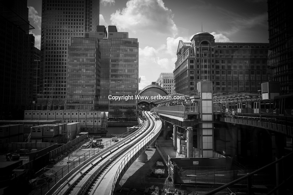 London. UK - DLR dockland light train, elevated subway in canary warf in the docklands, business , bank and office area under development , east of London
