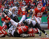 Kansas City Chiefs running back Larry Johnson (27) falls into the end zone for a touchdown past Jacksonville linebacker Brian Lwuh (59) in the first half at Arrowhead Stadium in Kansas City, Missouri, December 31, 2006.  The Chiefs beat the Jaguars 35-30.<br />