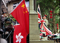 HONG KONG, CHINA - JULY 1, 1997: A man proudly puts up the Chinese and new Hong Kong Flag in photo on the left while the Union Jack comes down for the final time at the Centopath in Central Hong Kong as Hong Kong is handed back over to China after 150 years of British rule. Please go through the group to see more photos from that time.