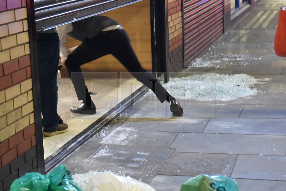 © Licensed to London News Pictures. 25/10/2019. London, UK. Shopkeepers clean up after a jewellers on Uxbridge Road was ram-raided buy three men in a black Rangerover in Shepherds Bush. Members of the public wrestled one of the robbers to the ground as who was apprehended by police in under a minute. The other two escaped on foot.  Photo credit: Guilhem Baker/LNP