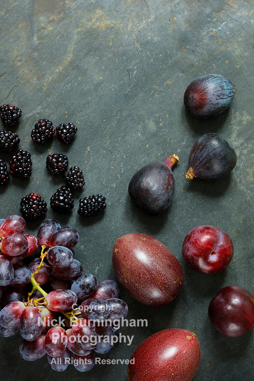 Dark Exotic Fruits on slate background including passion fruit, plums, figs, grapes, black berries, with copy space