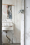 old dilapidated  restroom sink with mirror
