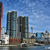 Emerging Barangaroo Skyline in Sydney, Australia<br /> This coastline along the southeastern mouth of today&rsquo;s Darling Harbour has a long history, starting as a native settlement over 14,000 years ago. Shortly after the British arrived in 1788, most of the Aboriginal people died from smallpox. During the 19th century, Millers Point grew as a village along with mills, warehouses and shipyards. During the first half of the 20th century, the area was severely impacted by bubonic plaque, the Great Depression and World War II. The next fifty years witnessed the rise and fall of commercial wharfs. In 2003, the NSW government announced a major new development project and named it Barangaroo in honor of a famous Aboriginal woman who died in 1791. These three office skyscrapers, known as International Towers Sydney, were built from 2013 to 2016. Additional residential, commercial, shopping and hotel properties are planned through 2023.