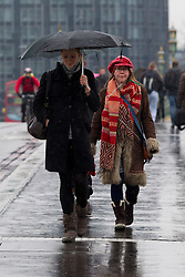 © Licensed to London News Pictures. 11/02/2013. London, UK. Commuters shelter under umbrellas during snowfalls on Westminster Bridge in London today (11/09/13). Britain awoke to more snowfalls this morning, with up to 4 inches in some of the worst hit areas. Photo credit: Matt Cetti-Roberts/LNP