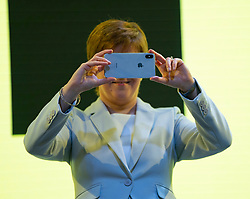 Edinburgh, Scotland, UK. 27 April, 2019. SNP ( Scottish National Party) Spring Conference takes place at the EICC ( Edinburgh International Conference Centre) in Edinburgh. Pictured; First Minister Nicola Sturgeon takes photo of the assembled delegates in the auditorium