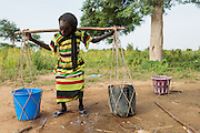 A girl balances water buckets on both ends of a stick as she prepares to carry them home from a UNICEF-sponsored, pedal-activated pump in the village of Game, Guera province, Chad on Tuesday October 16, 2012.