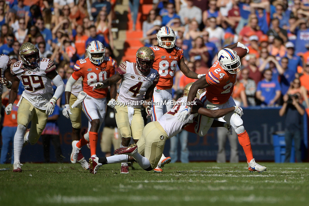 Florida running back Mark Thompson (24) is tackled by Florida State defensive back Nate Andrews (29) after rushing for yardage during the first half of an NCAA college football game Saturday, Nov. 25, 2017, in Gainesville, Fla. (Photo by Phelan M. Ebenhack)