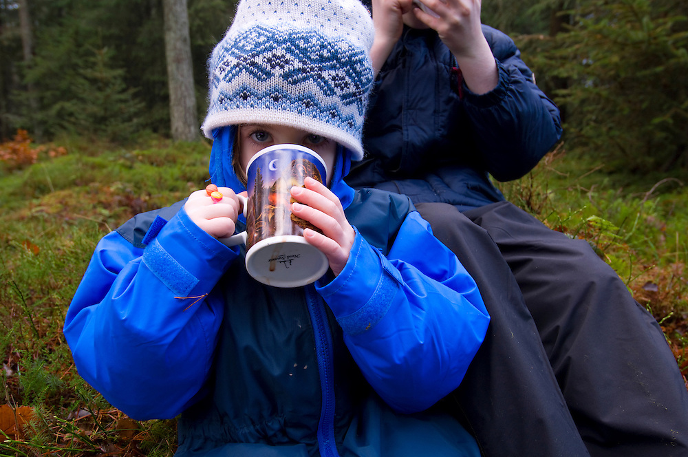 Children in the forest drinking hot chocolate