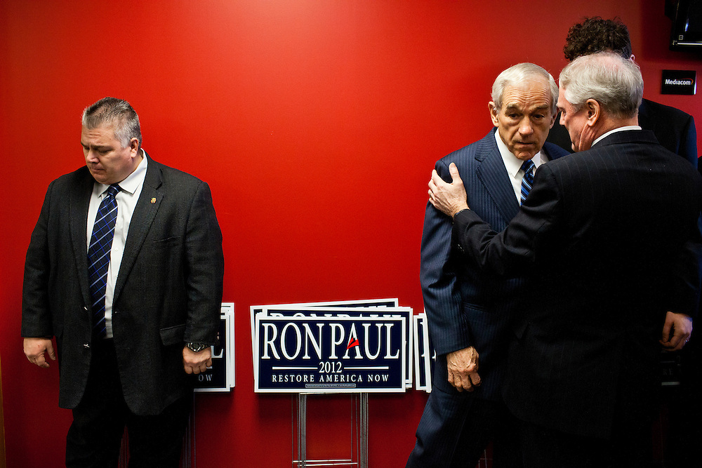 Republican presidential candidate Ron Paul talks with aides before a campaign town hall meeting on Wednesday, December 28, 2011 in Newton, IA.