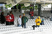 Spectators shelter from the heavy rain under the Compton stand ahead of the International Test Match 2019 match between England and Australia at Lord's Cricket Ground, St John's Wood, United Kingdom on 14 August 2019.