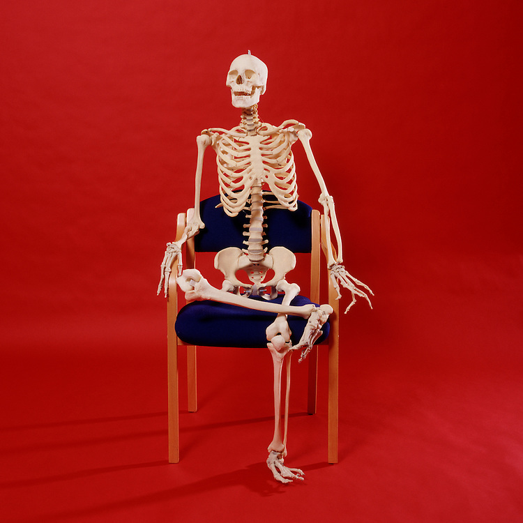 Skeleton relaxing back in a chair