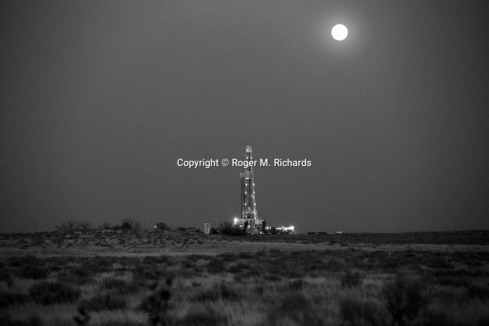 A drilling rig operates under a full moon in western Oklahoma. A boom in oil and gas drilling across the American West has led to pollution and environmental problems in what were once pristine lands. Traveling rigs go from location to location, drilling down into the shale rock, and are soon followed by pumps that inject a toxic brew of water and chemicals for hydraulic extraction or 'fracking' of oil and gas. Photograph by Roger M. Richards