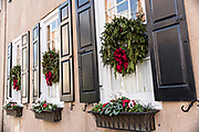 The windows of a historic home decorated with Christmas wreaths and window boxes on Meeting Street in Charleston, SC.
