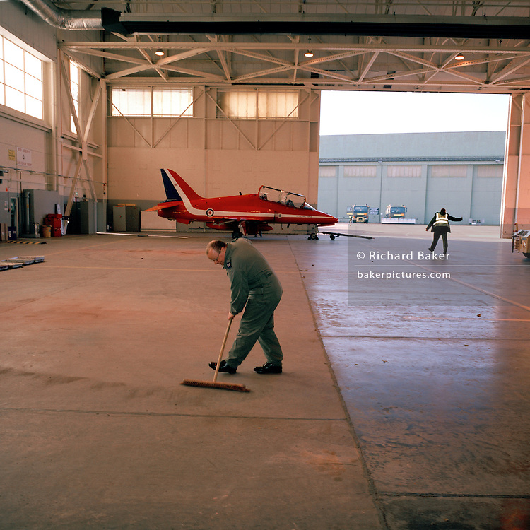 Ground staff sweeping the near-empty hangar of the Red Arrows, Britain's RAF aerobatic team.