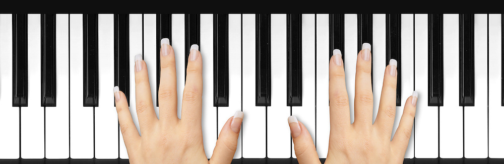 Two female hands with French manicured nails on piano keyboard