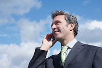 Business man talking on mobile phone outdoors
