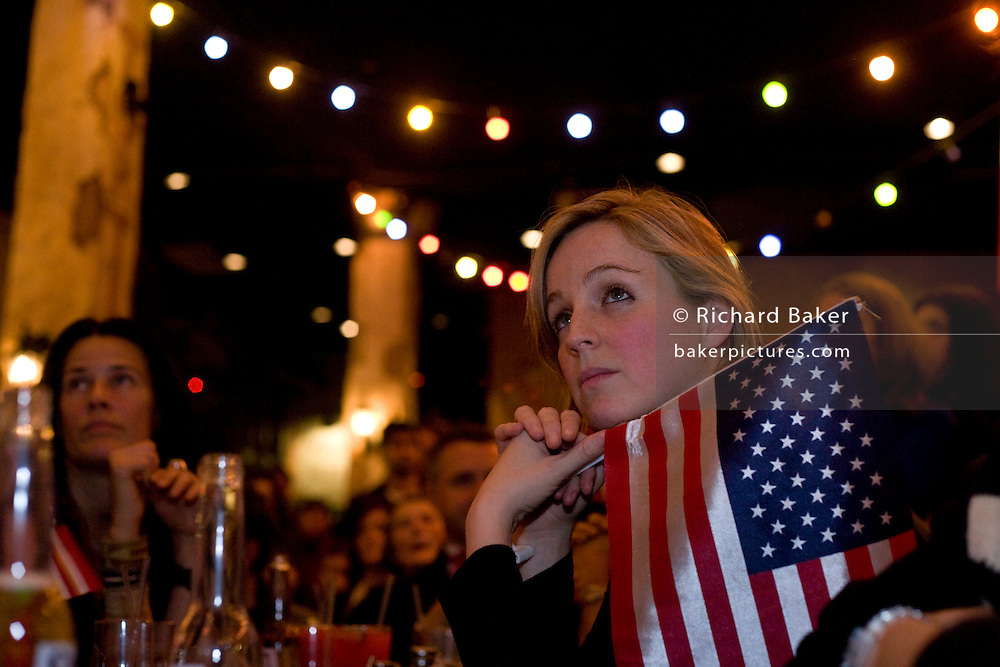 A US citizen listens spellbound to Barack Obama's inauguration speech. Along with other members of expatriate 'Democrats Abroad' party supporters, she holds the American flag during Obama's swearing in as the United States' 44th President, after his Nov 08 election victory as America's first African American Commander in Chief. The location is The Texas Embassy Texmex bar in central London, England. Similar events were held by Democrats Abroad around the world but in England, Obama's election to the White House excited Britain's political and cultural landscape during a deep economic recession. .