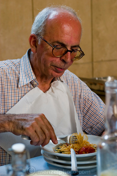 Riccardo Casagrande, a monk brother priest, eats spaghetti for lunch at the San Marcello al Corso Church in Rome, Italy, near the Spanish Steps.  (Riccardo Casagrande is featured in the book What I Eat: Around the World in 80 Diets.) Casagrande is in charge of the kitchen, garden, and wine cellar for the brotherhood. MODEL RELEASED.