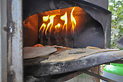 Outdoor Cooking preparing a flat bread Pita on a Saj - an iron dome shaped pan that is used to cook the pita bread on. It is placed over a source of heat, and the dough is placed on it to cook.
