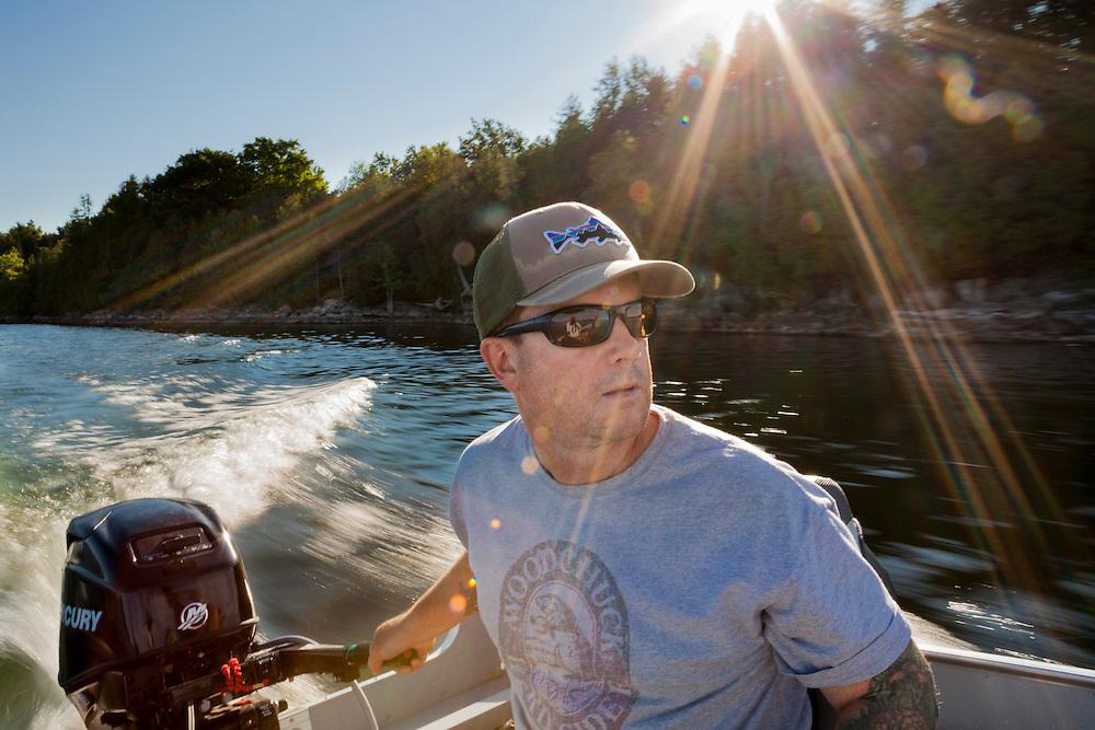 angler Kevin Favreau piloting a boat on lake champlain