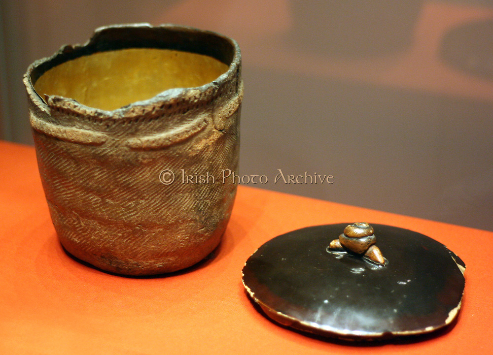 Jomon pot. This jomon cooking pot was about 2000 years earlier then flame and crown pots in the centre of the room. The rim is decorated with marks incised with a stick or finger nail and the cord markings are clearly visible. It was probably uncovered by a farmer in the 19th century and spotted by a tea master who thought it would make a fine water vessel (mizusashi) for a tea gathering. Gold leaf and lacquer was applied to the interior of the prehistoric vessel and a wodden lid was constructed with a snail decoration, alluding to the pot's unearthing from the soil.
