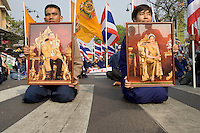 "BANGKOK, THAILAND  -  March 14: Protesters sit in the street with photos of the King and Queen of Thailand as tens of tousands of demonstrators seeking the resignation of Prime Minister Thaksin Shinawatra marched to government house on March 14, 2006 in Bangkok, Thailand. Marching several kilometers from the Grand Palace to Government House the protesters surrounded Thaksin's office chanting ""Thaksin Get Out"", as the Prime Minister threatened a state of emergency if the demonstration turned violent.  (Photo by David Paul Morris)"