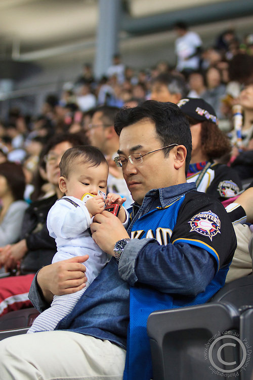A father and son watch a game of their home baseball team- the Hokkaido Nippon Ham Fighters - at the Sapporo Dome in Sapporo, Hokkaido