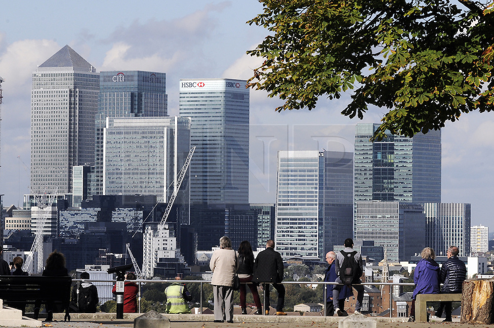 © Licensed to London News Pictures. 07/10/2014<br /> Canary Wharf from Greenwich Park.<br /> A sunny Autumn afternoon in Greenwich Park,Greenwich,London.<br /> (Byline:Grant Falvey/LNP)